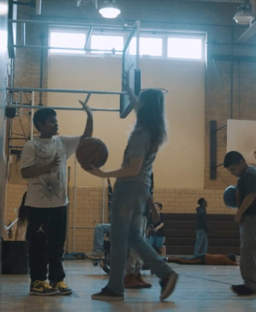Two students about to high-five in a school gym.