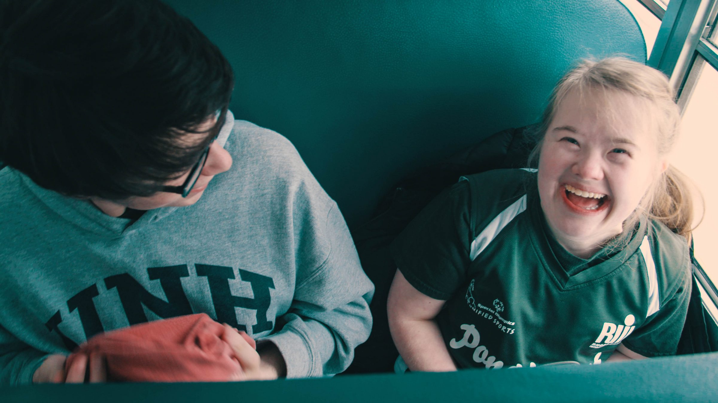 Kate DeCotis and a classmate sitting on the bus. Kate is smiling at the camera.