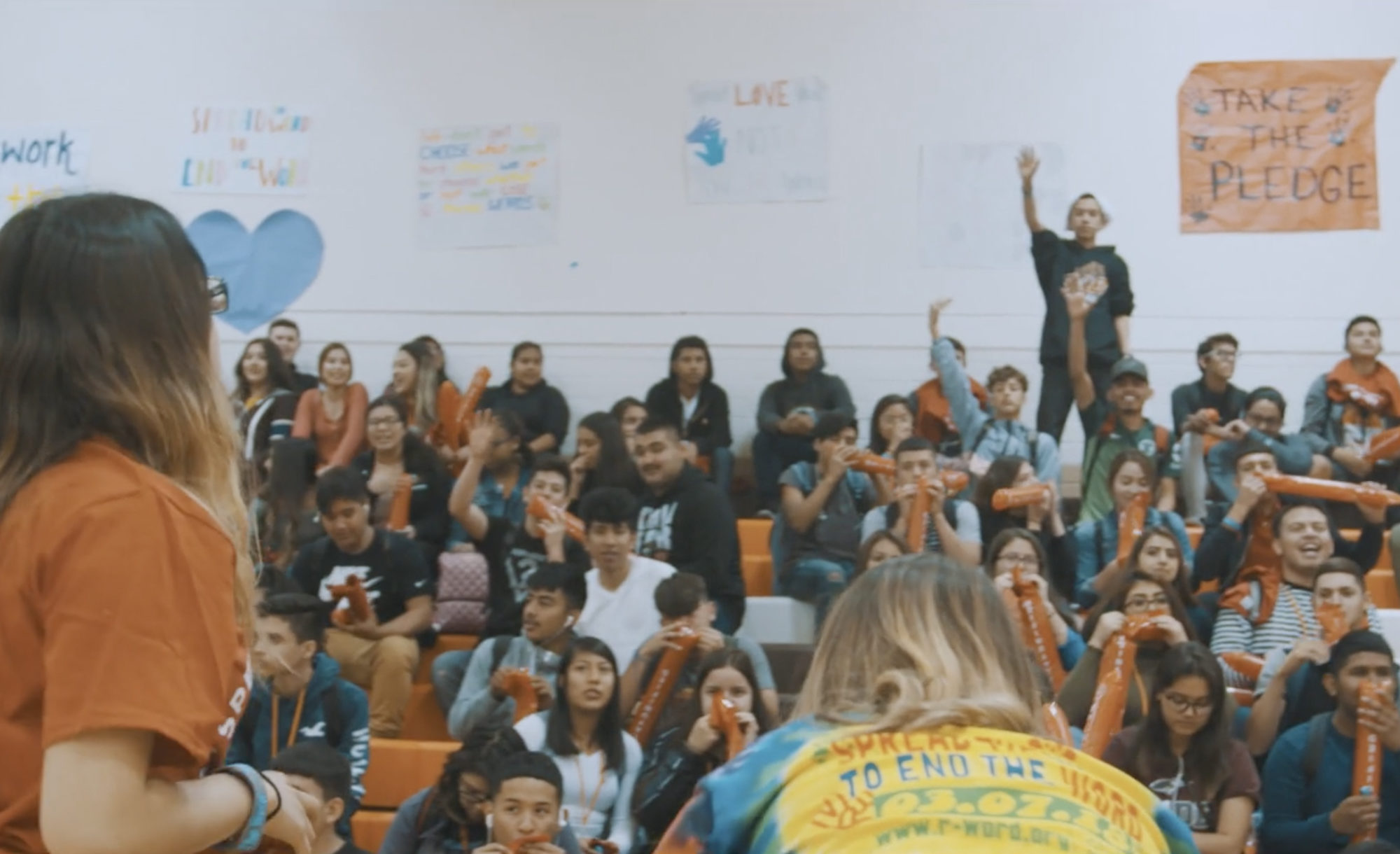 Students sitting in the bleachers of an assembly as two students face them.