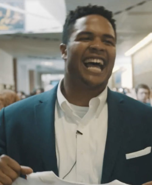 Eddie Yarbrough smiling as he walks down the hallway of his high school.