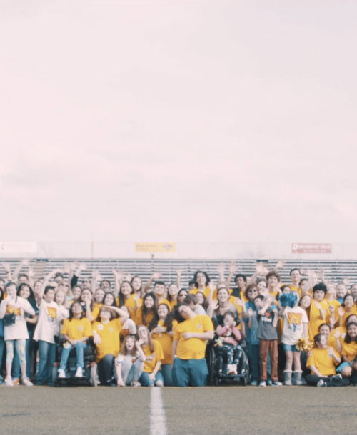 A group of students from Alamo Heights High School waving to the camera on a football field.