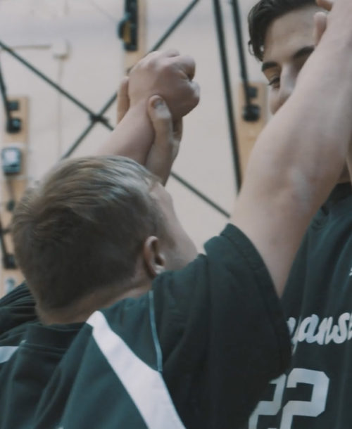 Two students from Ponaganset High School congratualting each other during a Unified Sports game.