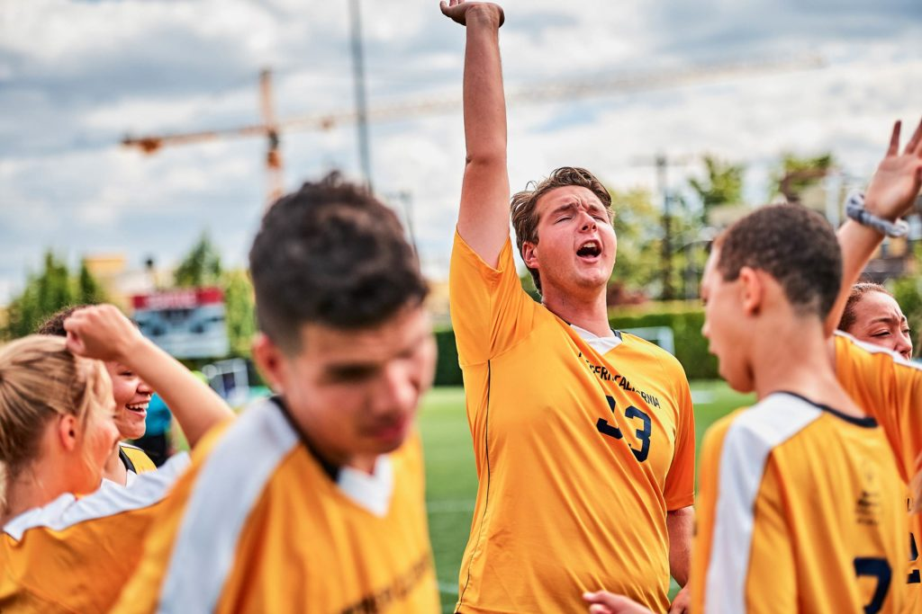 Young man with his team reaching his hand up in the air in triumph.