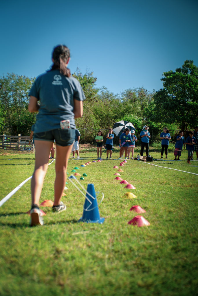 Student setting up another activity involving cones for Youth Sports Day.