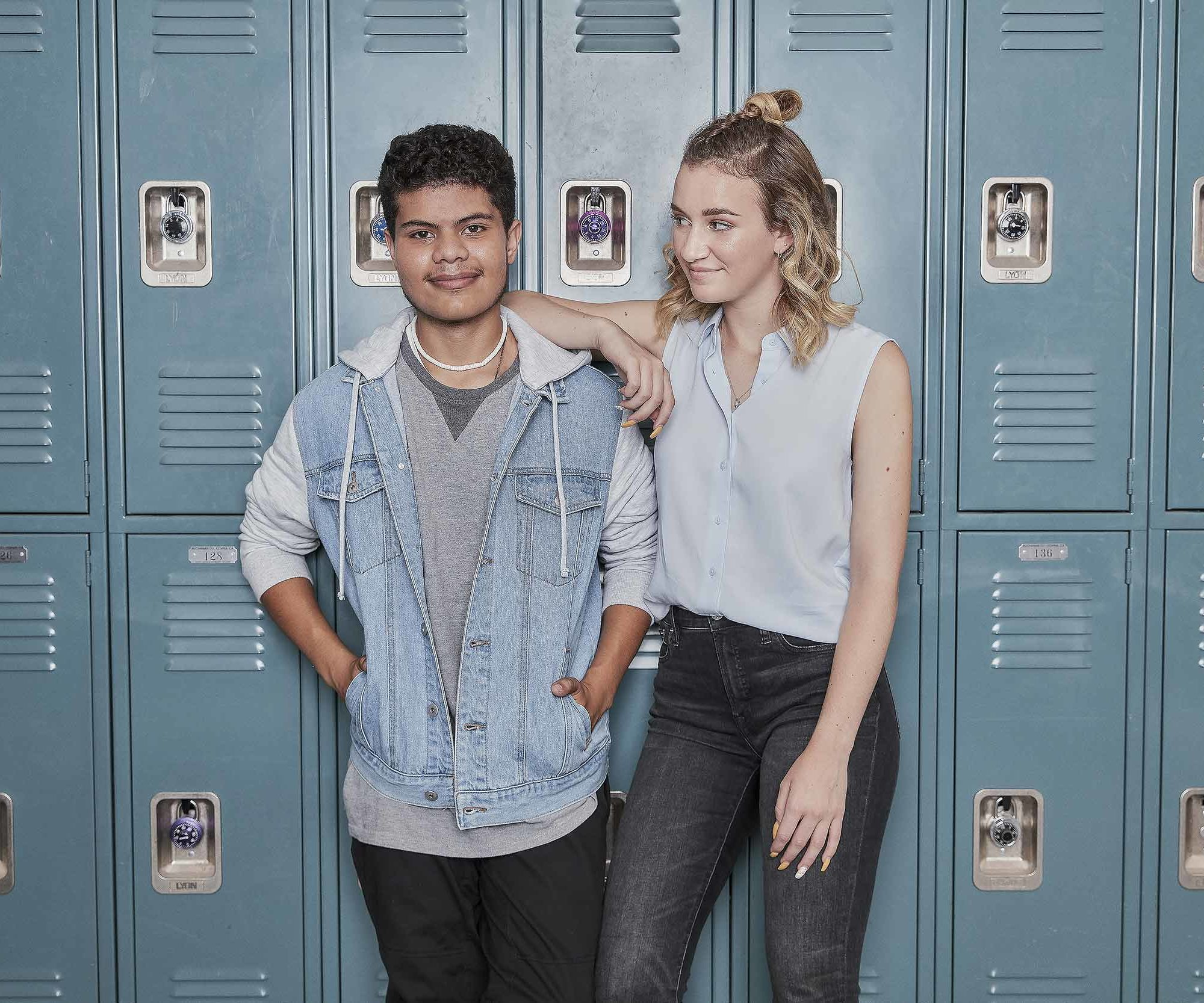 Two students standing in front of lockers.