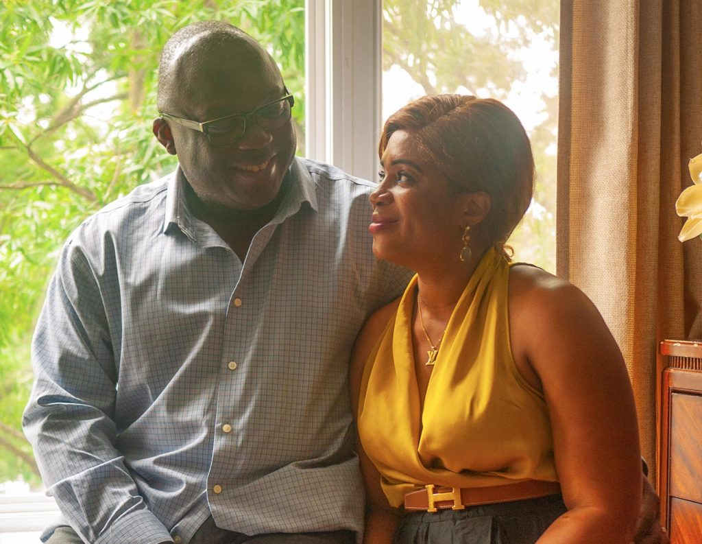 Claude and Catherine Dayas-Tokoto sitting in their home looking into each other's eyes.