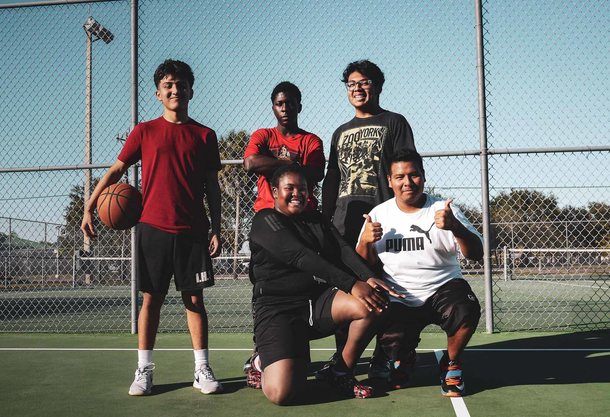 Students smiling for the camera on a basketball court.