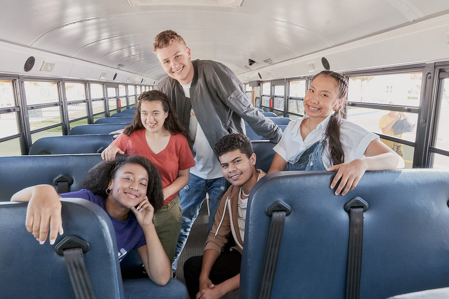 A group of students posing on a school bus.