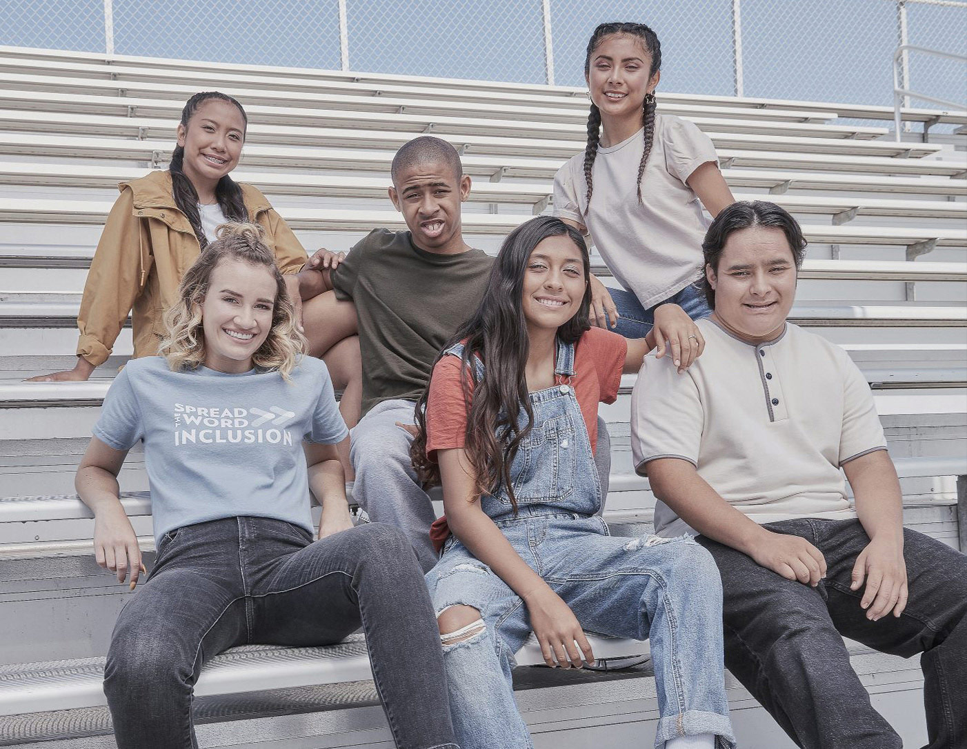 Group of students sitting on bleachers, smiling at the camera.