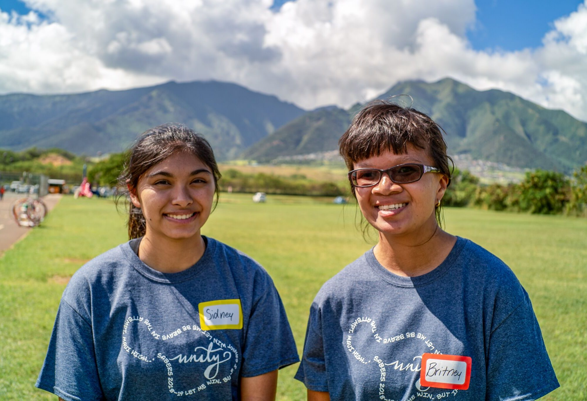 Two young women smiling at the camera with mountains and green grass in the background.