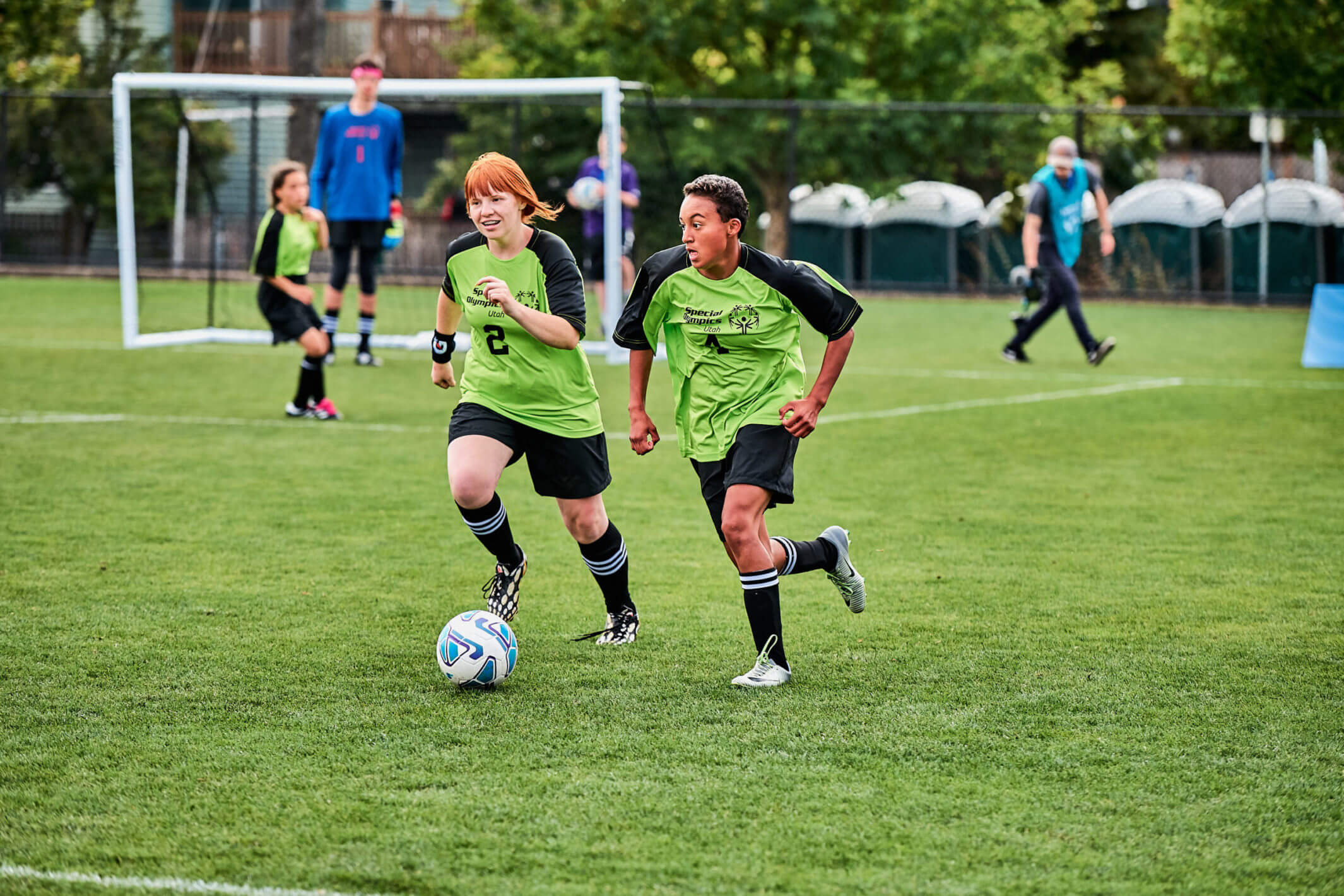 Two soccer players working together to dribble the ball down the field.