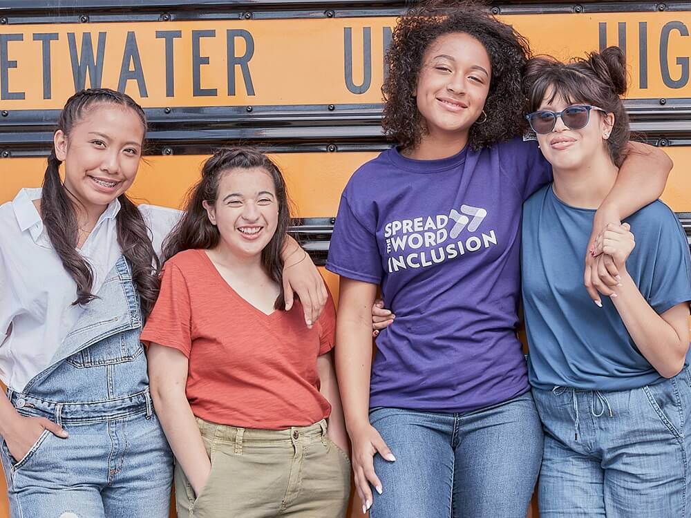 A group of four students pose in front of a school bus.