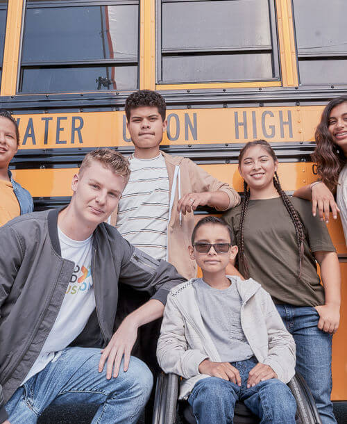 Group of students posing in front of a school bus.