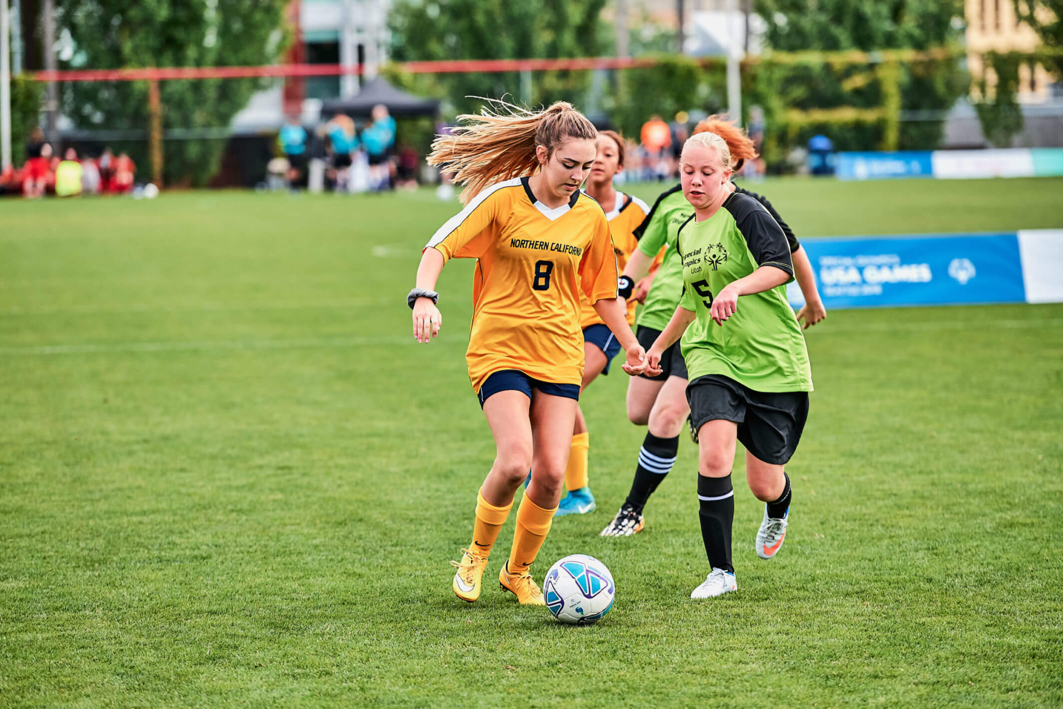 Two female students from opposing soccer teams fighting for the ball.