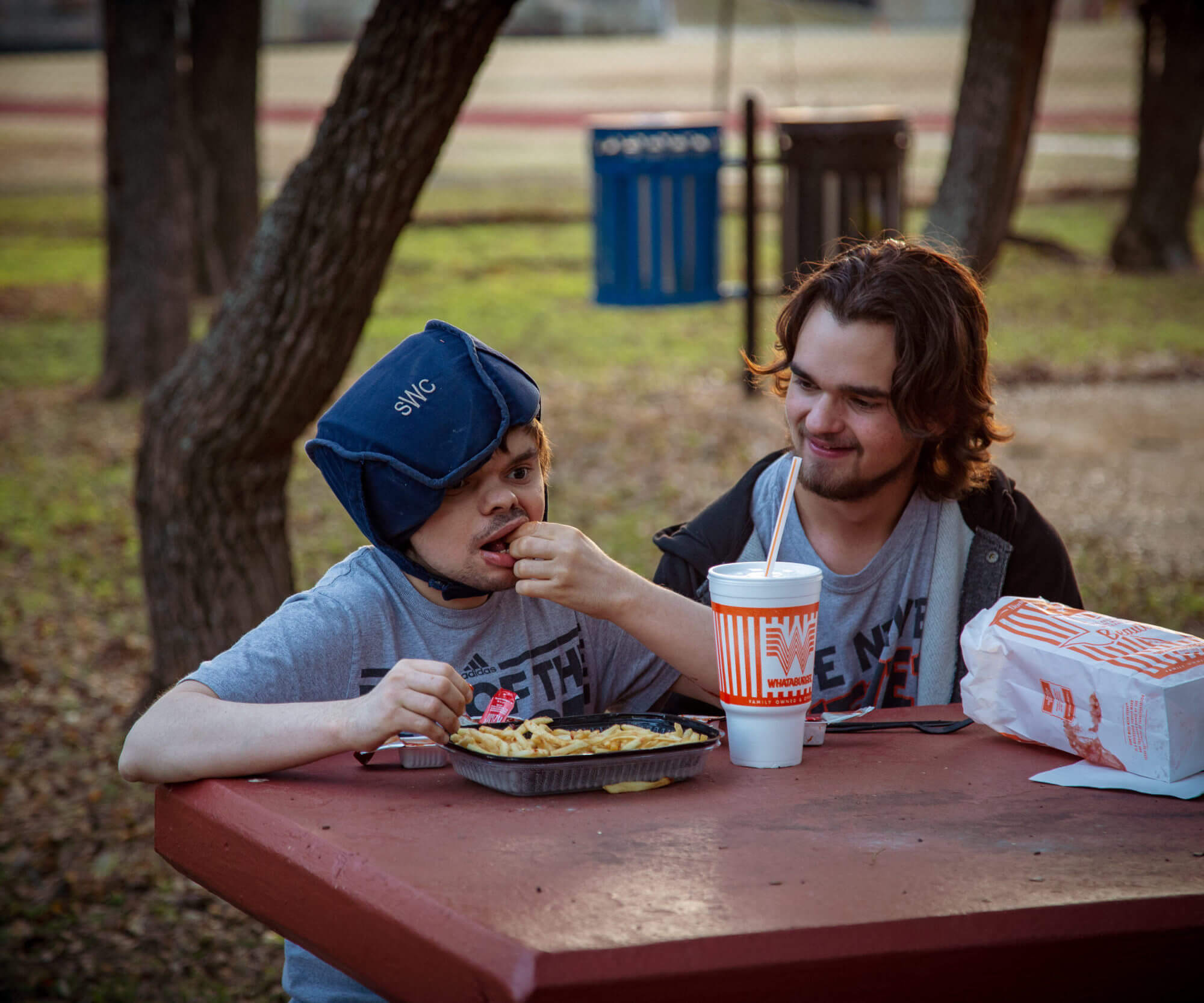 Sam (left) and his brother Noah (right) eating food together.