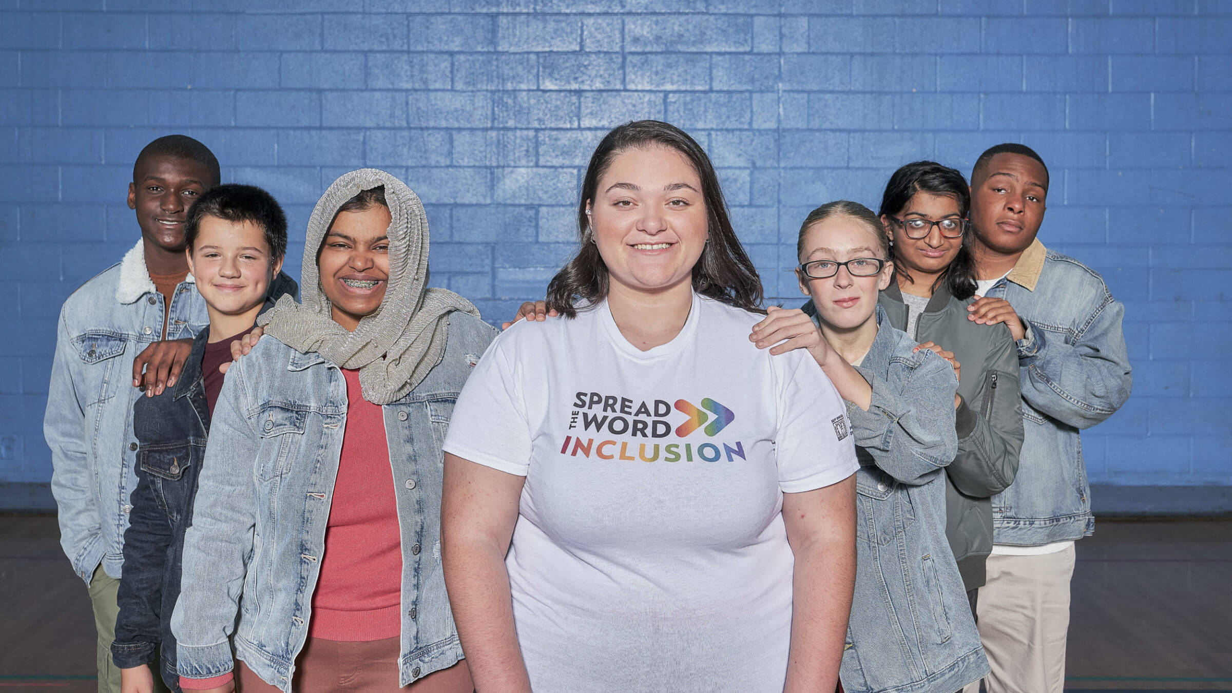 Group of students posing around one student wearing a Spread the Word shirt.