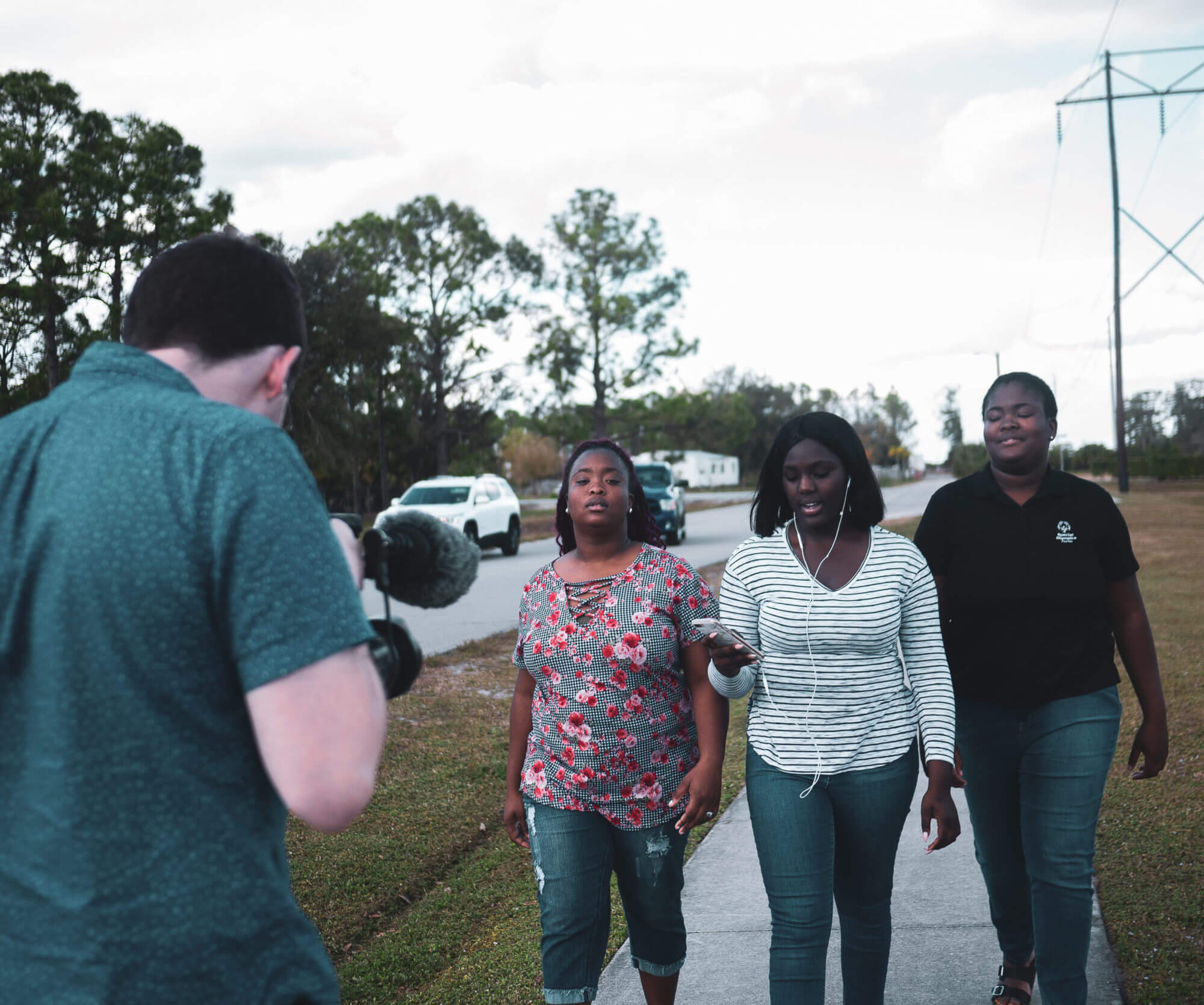 Walker filming Tajha and her sisters as they walk down the street