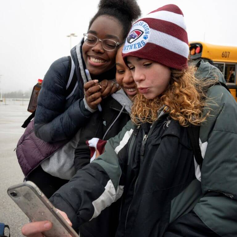 Three girls posing for a selfie. They are wearing winter gear and are standing in front of a school bus.
