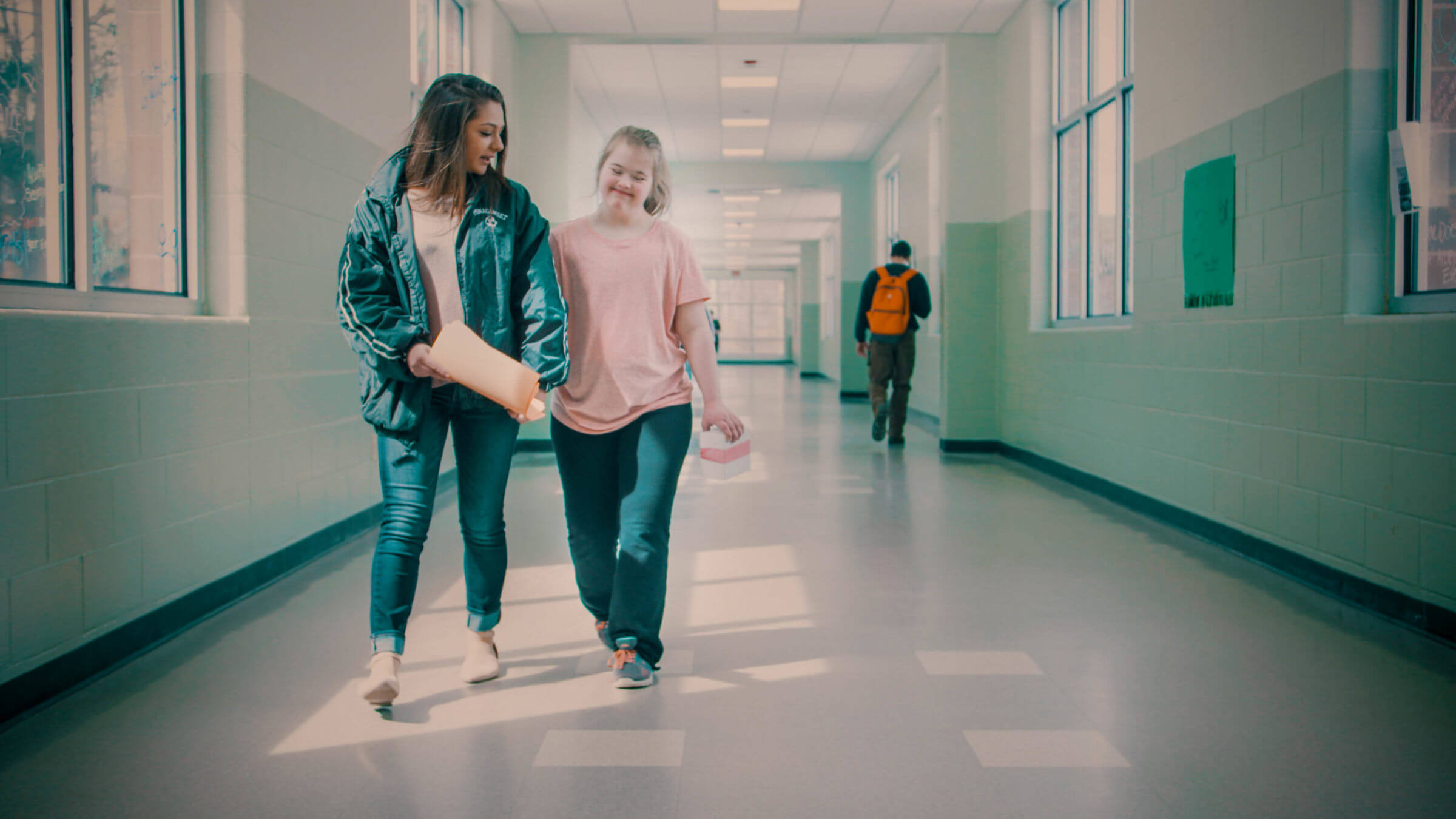 Emily and Kate walking down a school hallway.