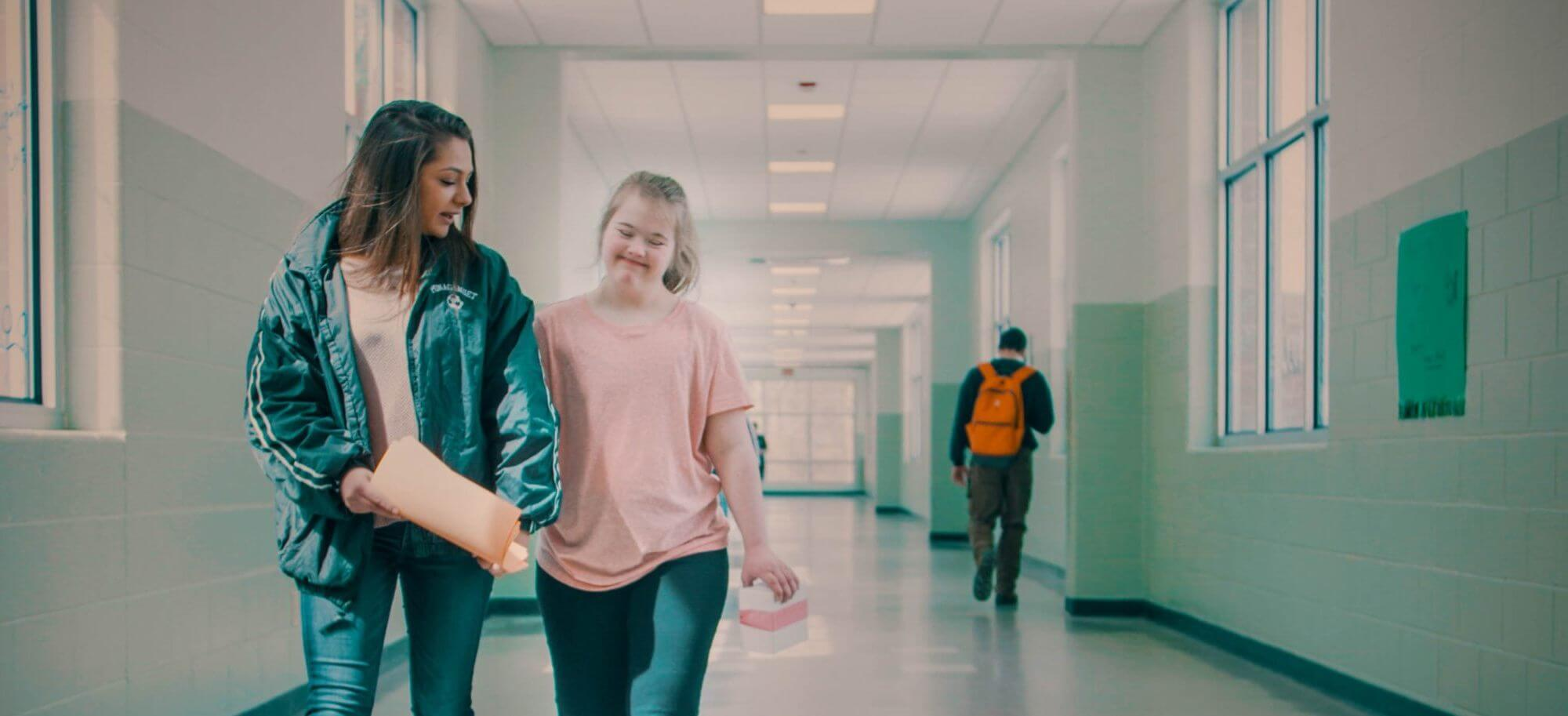 Emily and Kate walking down the school hallway.