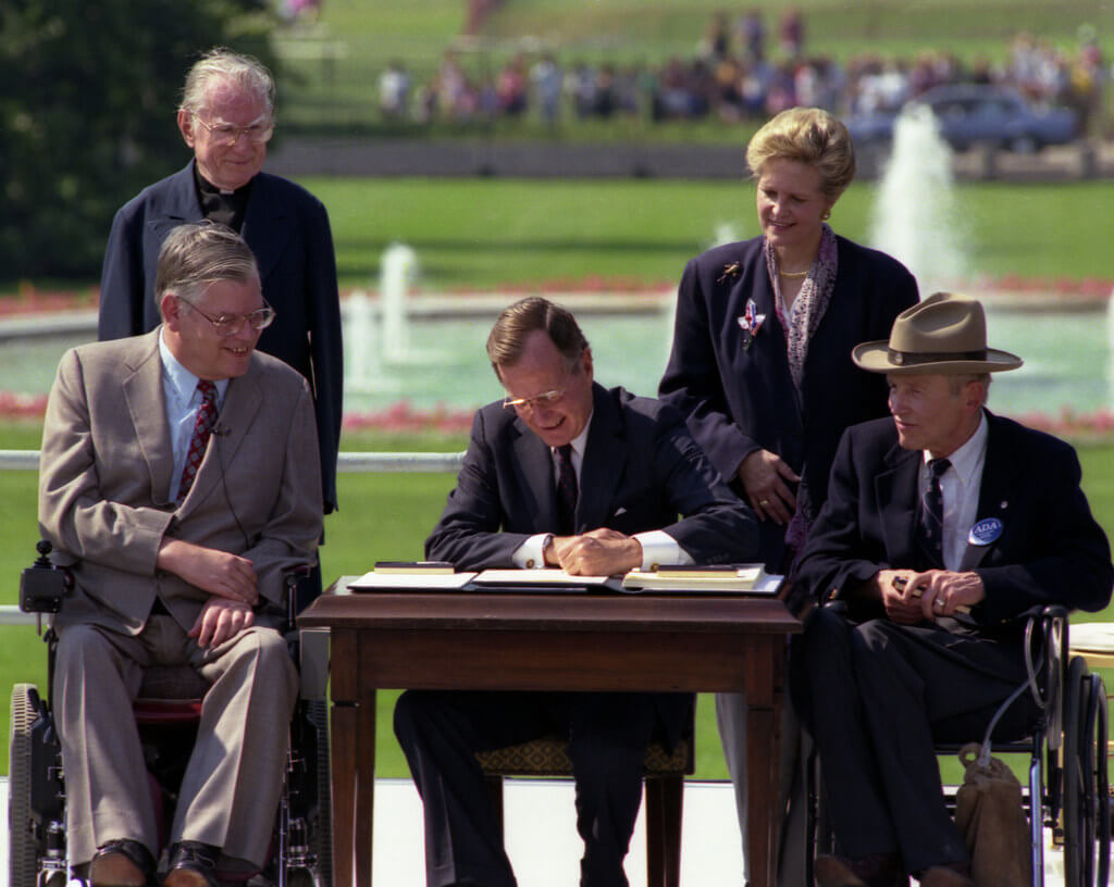 President George Bush signs into law the Americans with Disabilities Act of 1990 on the South Lawn of the White House. L to R, sitting: Evan Kemp, Chairman, Equal Employment Opportunity Commission, Justin Dart, Chairman, President's Committee on Employment of People with Disabilities. L to R, standing: Rev. Harold Wilke and Swift Parrino, Chairperson, National Council on Disability, 07/26/1990.