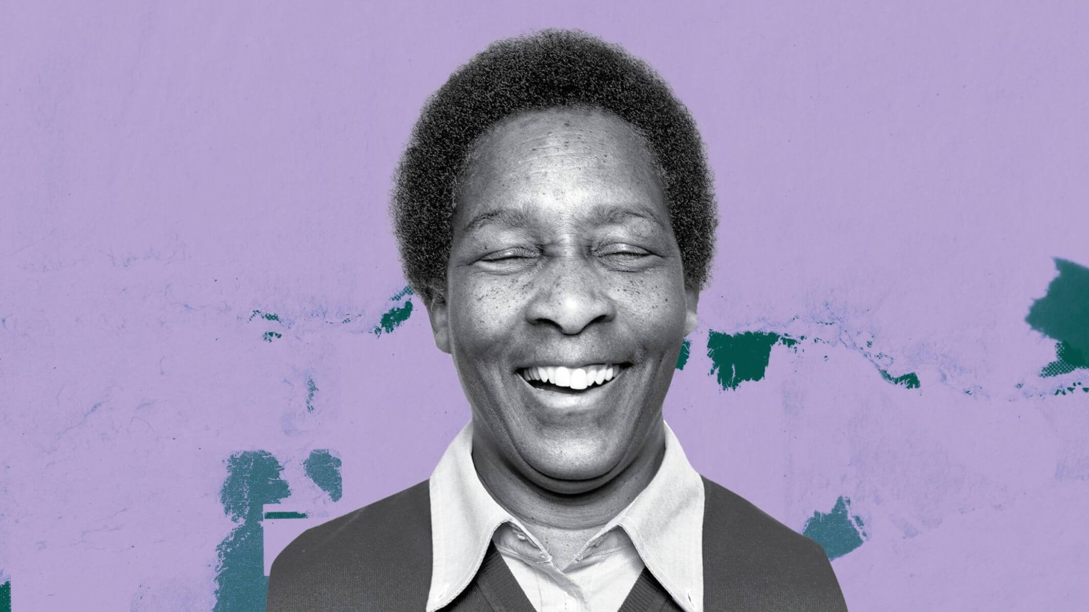An Image of Loretta Claiborne smiling with her eyes closed. She is in black and white but there is a colorful background behind her.
