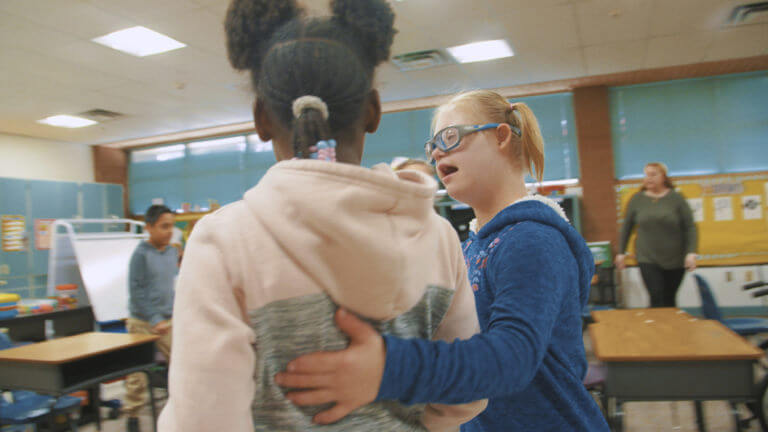 A student from Copper King Elementary puts her arm around another student.