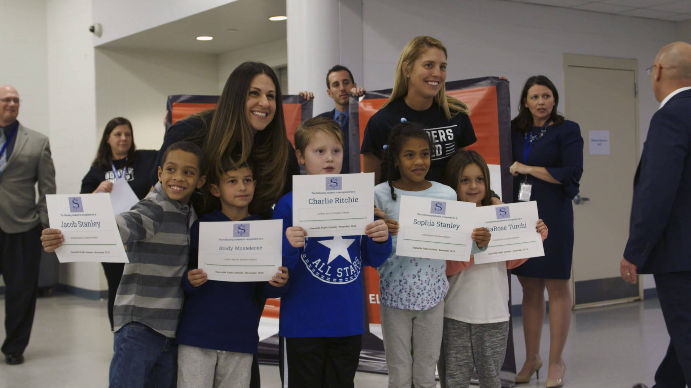 A group of students holding their certificates with two teachers standing behind them.