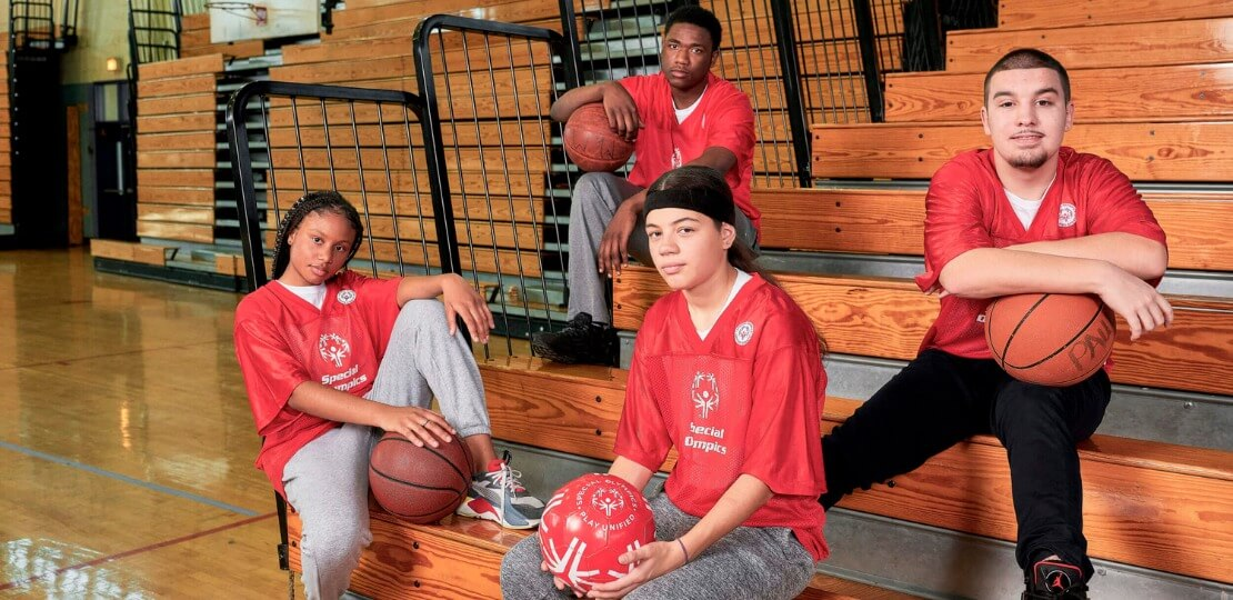 Four students sitting on school bleachers in red jerseys. Two of the students are female and two of the students are male.