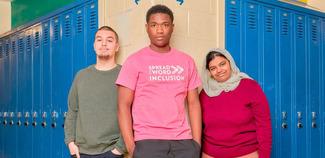 Three students standing alongside a row of lockers.