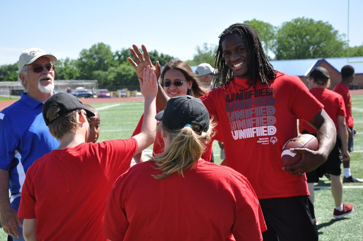 Former NFL running back Jamaal Charles gives high-fives to a group of Special Olympics athletes.