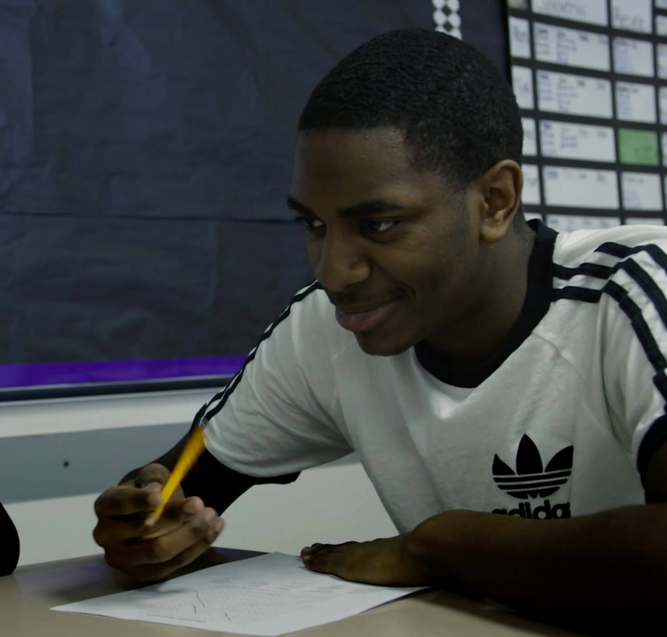 A student holding a pencil, smiling in class.